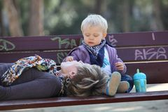 Closeness - Baby girl feeding her mother. Baby girl feeding her mother on bench in park Royalty Free Stock Photo