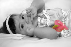 Baby girl with finger in her mouth and strawberry Royalty Free Stock Images