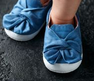 Baby girl first blue denim shoes with bow.  royalty free stock photos