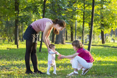 Baby girl first steps with mother and brother in a park Royalty Free Stock Image