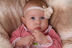 Baby girl with flower headband. On fluffy background royalty free stock photo
