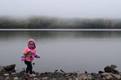 Baby girl at foggy lake royalty free stock images