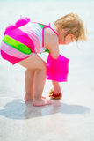 Baby girl found shell on sea shore. rear view Royalty Free Stock Photo