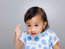 Baby girl frighten with finger. With gray background stock photo