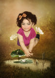 Baby girl, frog and fish Stock Photos