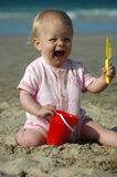 Baby girl fun screaming. A beautiful caucasian white blond baby girl in pink clothes with unhappy expression in her face screaming and holding her colorful beach Stock Image