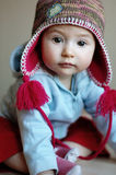 Baby girl in a funny cap. Sweet baby watching with interest Royalty Free Stock Photo