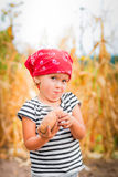 Baby girl on the garden with harvest of potato in her arms near field  dry corn  background. Dirty child in red bandana Stock Image