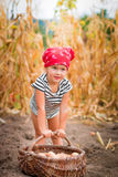 Baby girl on the garden with harvest of potatoes in the basket near field  dry corn  background. Dirty child in red Royalty Free Stock Images