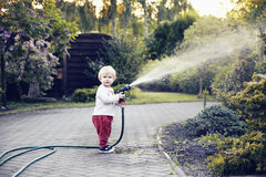 Baby girl with a garden hose Stock Photo