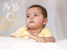 Baby girl gazing at letters and dazzle. Beautiful baby girl gazing at her A B C's and yellow dazzle Stock Image