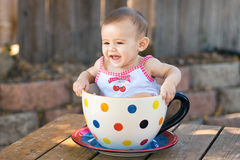 Baby girl in giant teacup royalty free stock images