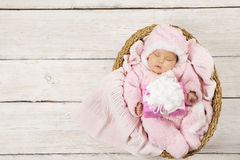 Baby girl with gift sleeping on wooden background, newborn in ba Stock Photos