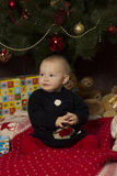 Baby girl with gifts under Christmas tree Royalty Free Stock Photo