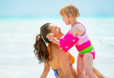 Baby girl giving mother listening sound of sea Royalty Free Stock Image