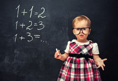 Baby girl  in glasses and chalk at a school board with arithmeti Stock Photography