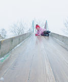 The baby girl goes with the ice slide on the street in winter Royalty Free Stock Photo