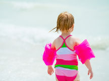 Baby girl going into sea. rear view Royalty Free Stock Photos