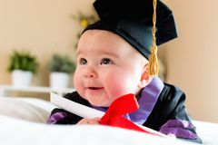 Baby girl in graduation cap and gown Stock Photo