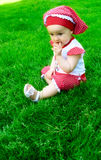 A baby girl on the grass Stock Image