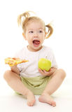 Baby girl with green apple and pizza Stock Photography