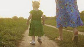 Baby girl in green dress and her mum walk along rural field pathway together on a sunny summer evening. Baby girl in green dress and her mum walk along rural stock video