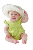 Baby girl in green dress sits wearing big straw hat Stock Photos