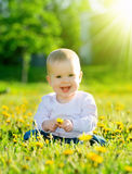 Baby girl on a green meadow with yellow flowers dandelions on th stock photos