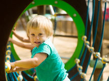 Baby girl in green at   playground in summer Stock Photos