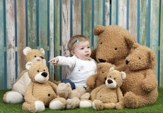 Baby girl with group of teddy bears, seated on grass Royalty Free Stock Photos