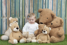 Baby girl with group of teddy bears, seated on grass royalty free stock photo