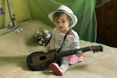 Baby girl with guitar sitting on the bed Stock Photos