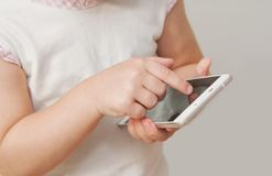 Baby girl hand pointing white smart phone  on white background Stock Images