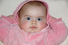 Baby girl with hands behind her head and a serious expression Royalty Free Stock Photo