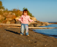 Baby girl is happy at the beach Stock Image