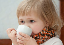 The baby girl has tea Royalty Free Stock Image