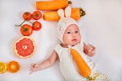 Baby girl in hat with bunny ears lies on white background with fruits and vegetables - healthy food, carrots, tomatoes, orange, le royalty free stock image