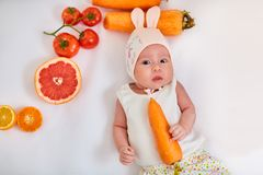 Baby girl in a hat with bunny ears lies on a white background with fruits and vegetables and holds a carrot in her hand - healthy stock photo