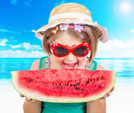 Baby girl in the hat eagerly eats juicy watermelon on sea background Royalty Free Stock Photography