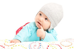 Baby girl with hat lying on a duvet Stock Photo