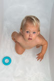 Baby girl is having a bath. Baby sitting in water in a bath and playing with colourful balls. Close portrait Royalty Free Stock Images