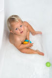 Baby girl is having a bath. Baby sitting in water in a bath and playing with colourful balls. Close portrait Stock Photos