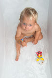 Baby girl is having a bath. Baby sitting in water in a bath and playing with colourful balls. Close portrait Stock Photo