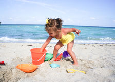 Baby girl is having fun at the beach Stock Image