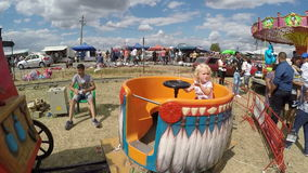 Baby girl having fun in a fair country carousel stock footage