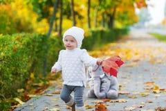 Baby girl having fun in fall park Stock Photos