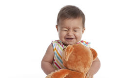 Baby girl having fun with her toy bear Stock Images