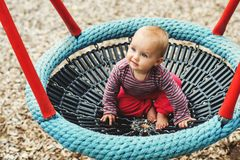 Adorable baby girl playing outside. Baby girl having fun in the park, 9-12 months old kid playing in the big swing, summer playground, activities for children Stock Photography