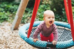 Adorable baby girl playing outside. Baby girl having fun in the park, 9-12 months old kid playing in the big swing, summer playground, activities for children Stock Image