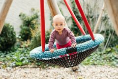 Adorable baby girl playing outside. Baby girl having fun in the park, 9-12 months old kid playing in the big swing, summer playground, activities for children Royalty Free Stock Photos